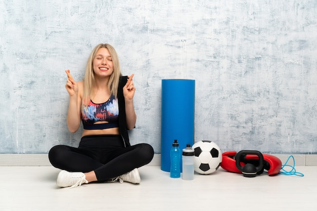 Young blonde sport woman sitting on the floor with fingers crossing
