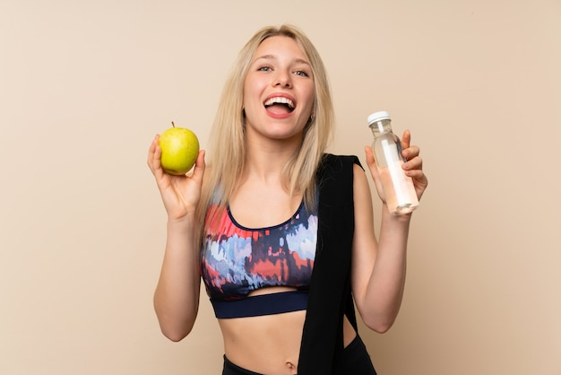 Young blonde sport woman with an apple and a bottle of water