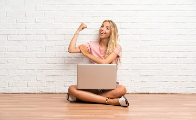 Young blonde student girl with a laptop on the floor making strong gesture