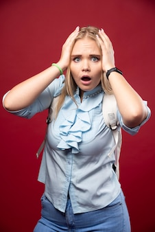 젊은 금발 여학생은 학교로 돌아가 우울하고 긴장한 모습을 보인다.