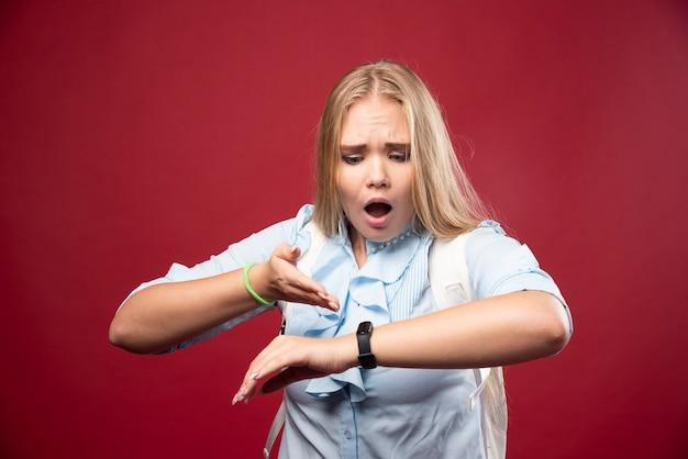 젊은 금발 여학생은 학교로 돌아가 시간을 확인하고 늦으면서 스트레스를 받는다.