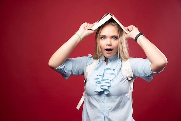 젊은 금발 학생 여자는 그녀의 책을 머리에 들고 피곤하고 혼란스러워 보입니다.