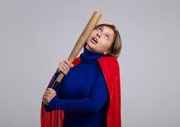 コピースペースで白い背景に分離された野球のバットを見上げて頭の中で自分自身を打つ赤いマントの若いブロンドのスーパーヒーローの女の子