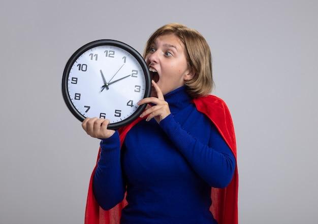 Молодая блондинка супергерой девушка в красном плаще держит и смотрит на часы, пытаясь укусить их, изолированные на белом фоне с копией пространства