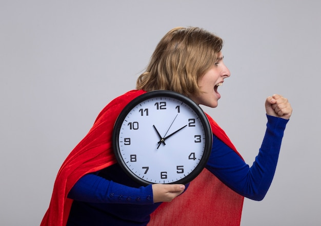 Молодая блондинка супергерой девушка в красном плаще, стоя в профиль, глядя прямо сжимая кулак, держа часы, кричащие, изолированные на белой стене