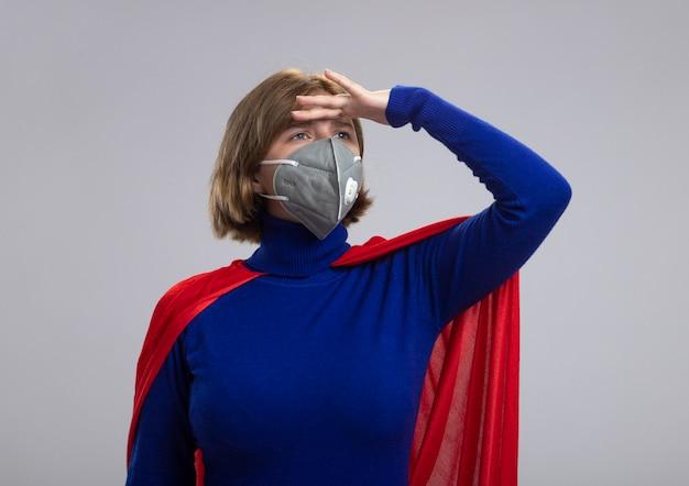 保護マスクを身に着けている赤いマントの若いブロンドのスーパーヒーローの女の子は、白い背景で隔離の距離に横を見て額に手を保ちます