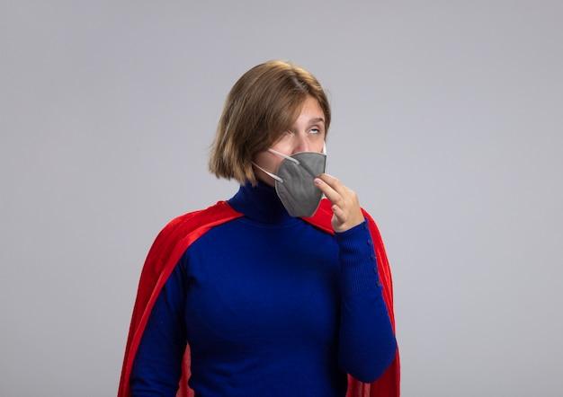 Молодая блондинка супергероя в красной накидке в защитной маске пытается снять ее, закатывая глаза, изолированные на белом фоне с копией пространства