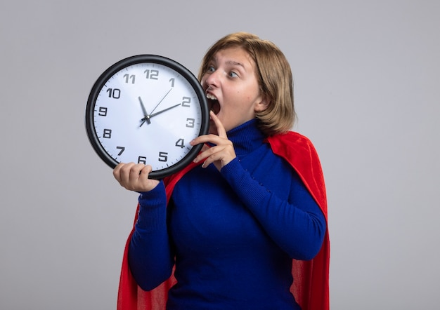 Giovane ragazza bionda del supereroe in mantello rosso che tiene e guardando l'orologio cercando di morderlo isolato su priorità bassa bianca con lo spazio della copia