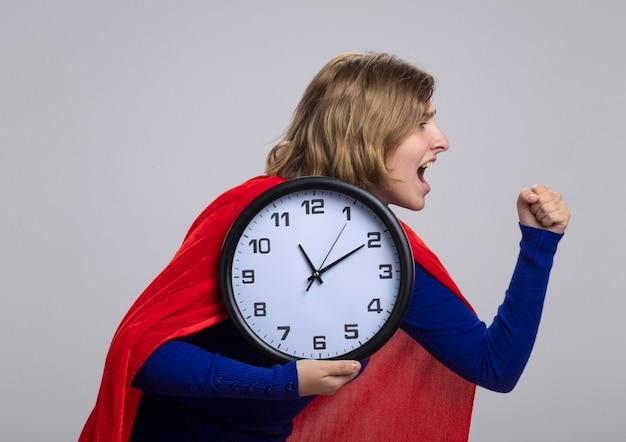 Giovane ragazza bionda del supereroe in mantello rosso in piedi nella vista di profilo guardando dritto pugno di serraggio tenendo l'orologio urlando isolato sul muro bianco
