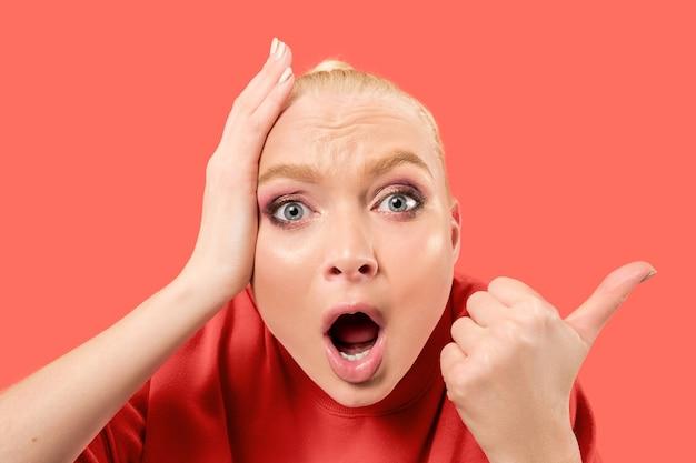 Giovane donna bionda sorpresa che grida su sfondo di corallo