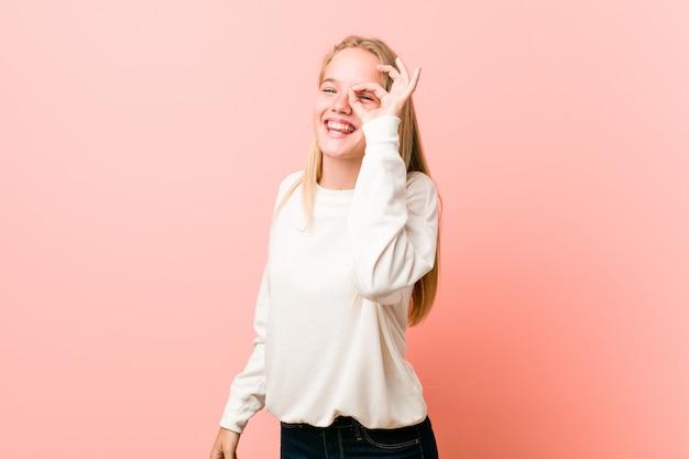 Young blonde teenager woman excited keeping ok gesture eye.
