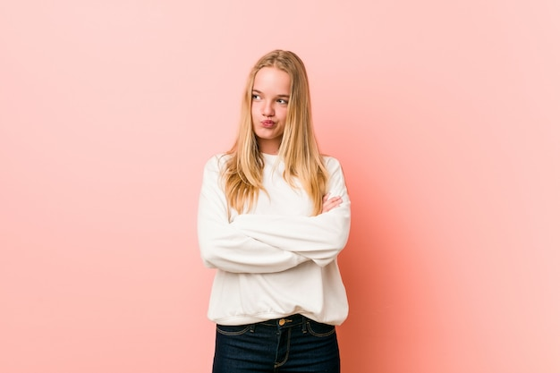 Young blonde teenager woman frowning face in displeasure, keeps arms folded.