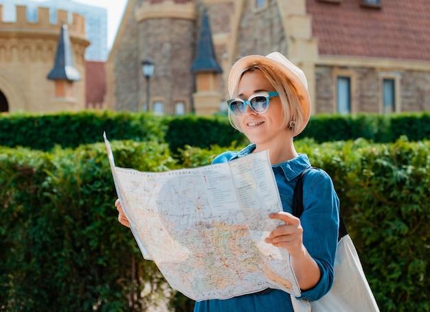 다른 나라의 명소의지도와 모자와 선글라스에 젊은 금발 여행자 여자. 여름 휴가 및 활동적인 레크리에이션의 자유와 활동적인 라이프 스타일 개념