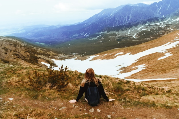 Young blonde travels with a blue backpack, sits on top of a mountain and enjoys green mountain scenery