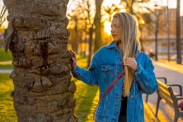 Young blonde in a tree with a denim jacket