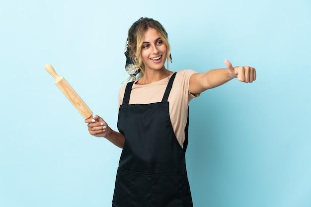 Молодая блондинка уругвайская кулинария изолирована, показывая палец вверх