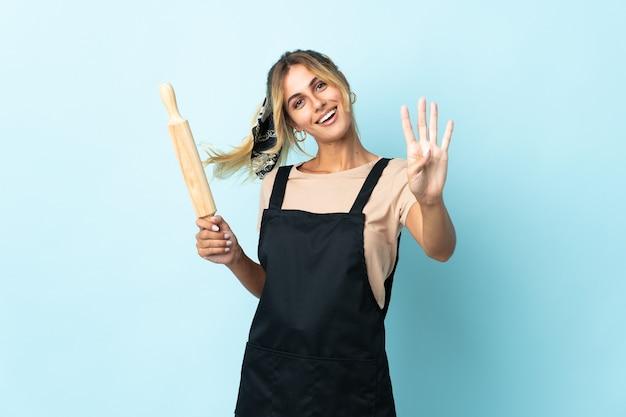 Молодая блондинка уругвайская кулинария изолирована счастливой и считает четыре пальцами