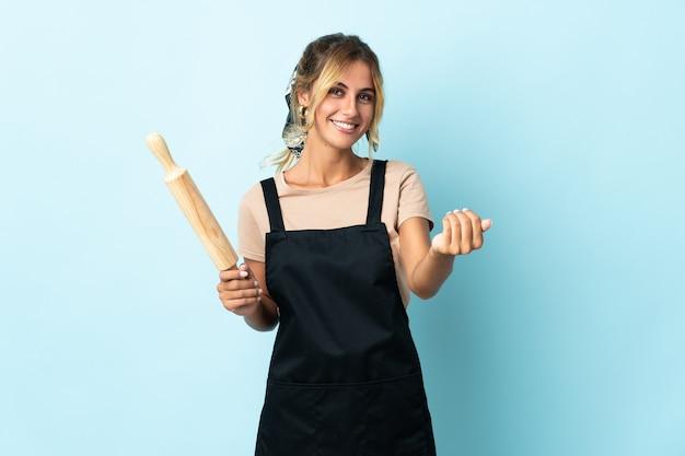 Молодая блондинка уругвайская кулинария изолирована, приглашая прийти с рукой