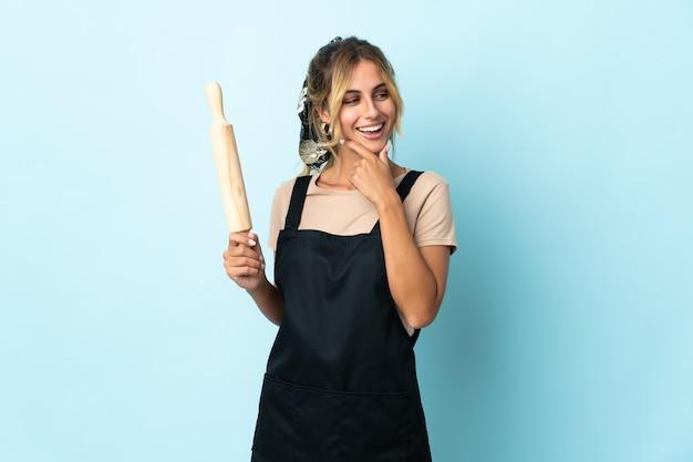 Молодая блондинка уругвайская кулинария женщина изолирована, глядя в сторону и улыбается