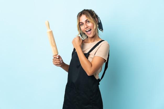 Молодая блондинка уругвайская кулинария женщина изолирована на синем, празднует победу