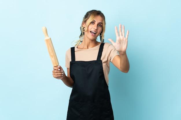 Молодая блондинка уругвайская кулинария изолирована на синем, считая пять пальцами
