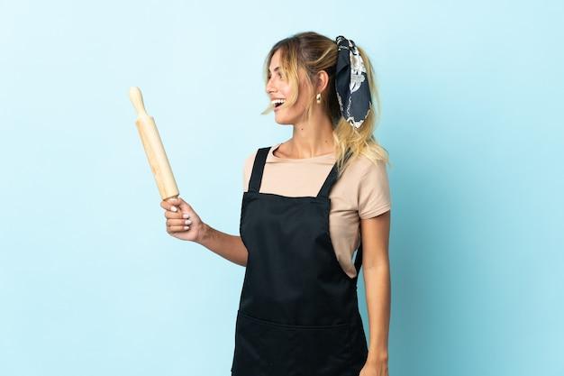 Молодая блондинка уругвайская кулинария изолирована на синем, смеясь в боковом положении