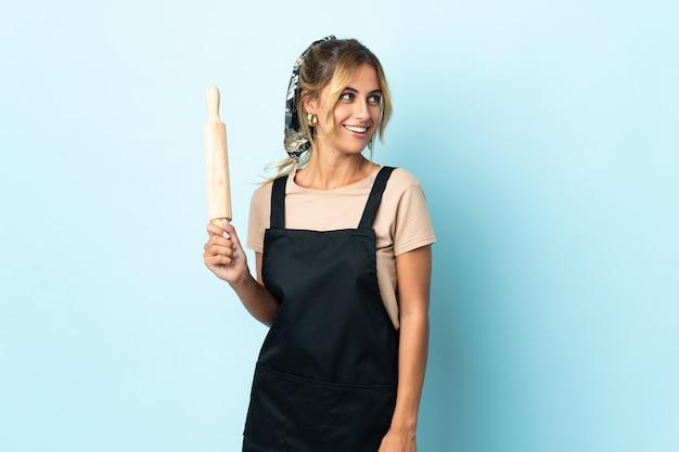 Молодая блондинка уругвайская кулинария женщина изолирована на синей стороне