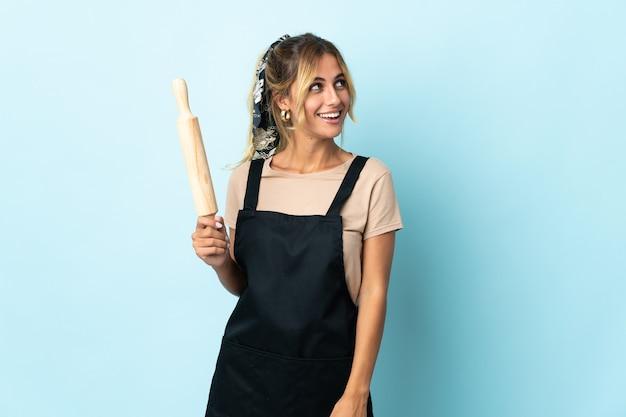 Молодая блондинка уругвайская кулинария женщина изолирована на синем, смотрит в сторону и улыбается