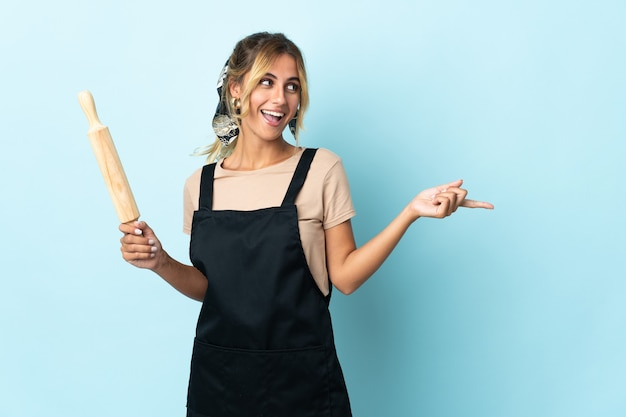 Молодая блондинка уругвайская кулинария изолирована на синем указательном пальце в сторону и представляет продукт