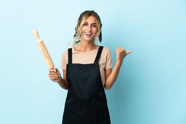 Молодая блондинка уругвайская кулинария изолирована на синем, указывая в сторону, чтобы представить продукт