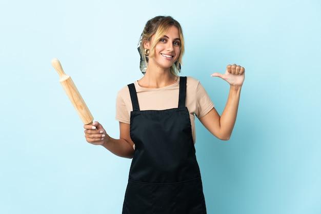 Молодая блондинка уругвайская кулинария изолирована на синем, гордом и самодовольном