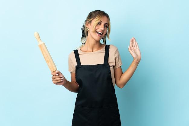 Молодая блондинка уругвайская кулинария изолирована на синем салюту рукой с счастливым выражением лица