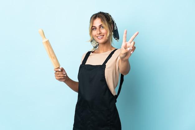 Молодая блондинка уругвайская кулинария женщина изолирована на синем, улыбаясь и показывая знак победы