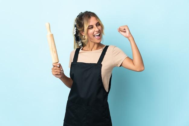 Молодая блондинка уругвайская кулинария женщина изолирована на синей стене празднует победу