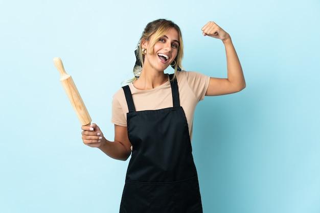 Молодая блондинка уругвайская кулинария женщина изолирована на синей стене, делая сильный жест