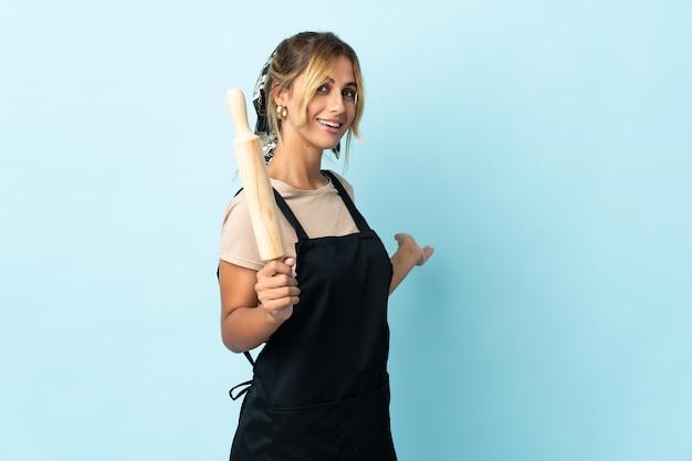 Молодая блондинка уругвайская кулинария изолирована на синей стене, протягивая руки в сторону, чтобы пригласить приехать