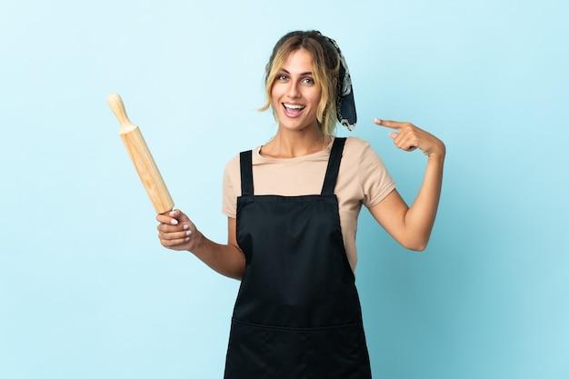 Молодая блондинка уругвайская кулинария изолирована на синей стене, показывая большой палец вверх