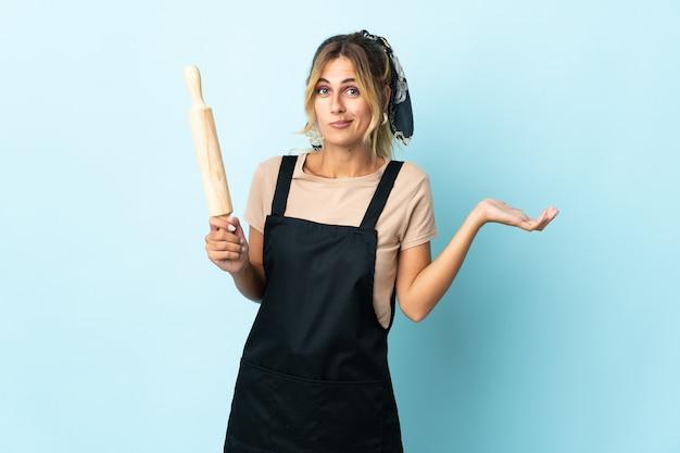 Молодая блондинка уругвайская кулинария изолирована на синей стене, сомневаясь, поднимая руки