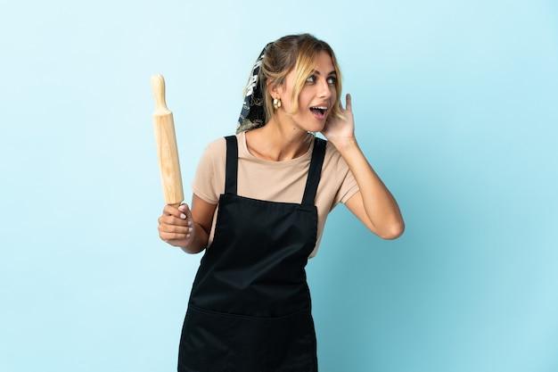 Молодая блондинка уругвайская кулинария изолирована на синей стене, слушая что-то, положив руку на ухо