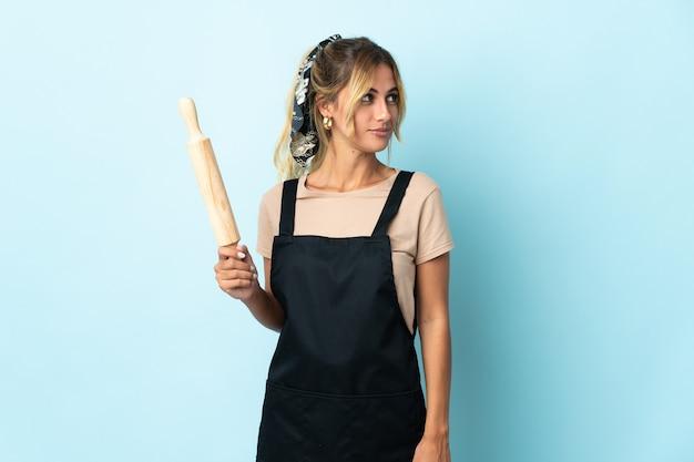 Молодая блондинка уругвайская кулинария женщина изолирована на синей стене, глядя в сторону