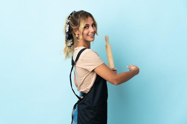 Молодая блондинка уругвайская кулинария женщина изолирована на синей стене, указывая назад
