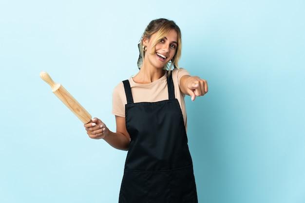 Молодая блондинка уругвайская кулинария изолирована на синей стене, указывая вперед с счастливым выражением лица