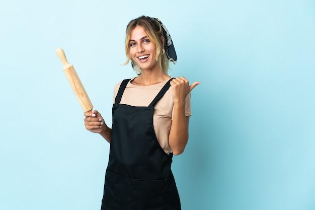 Молодая блондинка уругвайская кулинария изолирована на синей стене, указывая в сторону, чтобы представить продукт