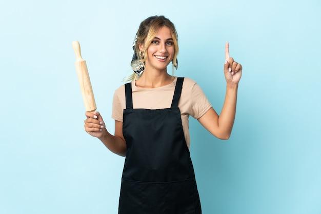 Молодая блондинка уругвайская кулинария изолирована на синей стене, указывая на отличную идею
