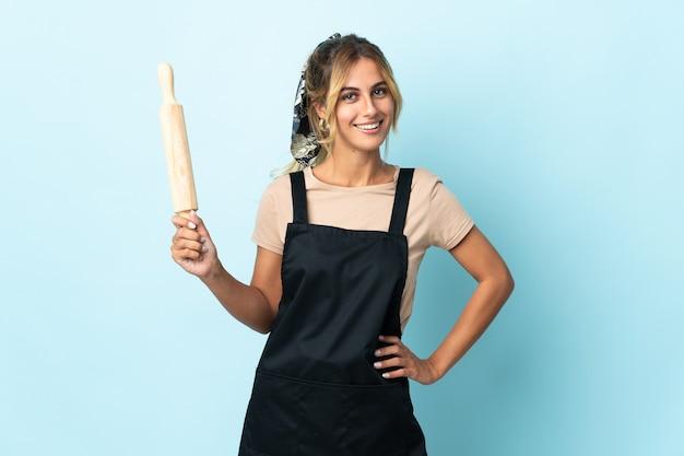 Молодая блондинка уругвайская кулинария женщина изолирована на синей стене позирует с руками на бедрах и улыбается