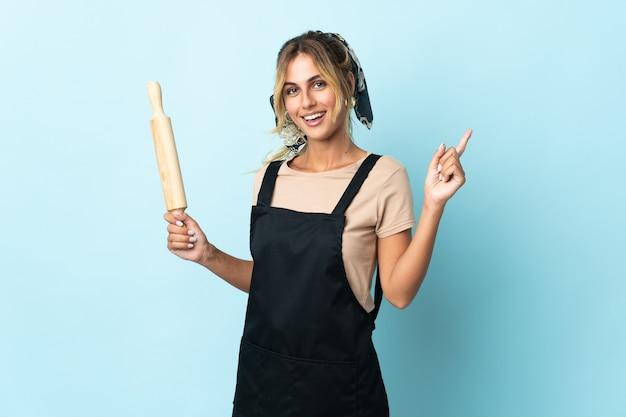 Молодая блондинка уругвайская кулинария изолирована на синей стене, показывая и поднимая палец в знак лучших