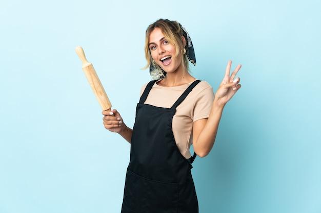 Молодая блондинка уругвайская кулинария женщина изолирована на синей стене улыбается и показывает знак победы