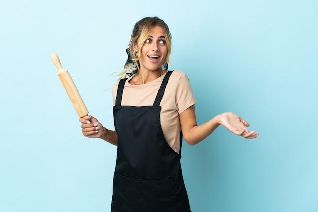 Молодая блондинка уругвайская кулинария изолирована на синей стене с удивленным выражением лица, глядя в сторону