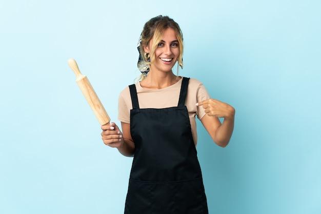 Молодая блондинка уругвайская кулинария изолирована на синей стене с удивленным выражением лица
