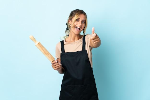 Молодая блондинка уругвайская кулинария изолирована на синей стене с большими пальцами руки вверх, потому что произошло что-то хорошее